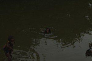 Kinder im schmutzigen Wasser