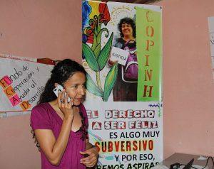 La Esperanza: Berta Zúniga telefoniert vor einem Copinh-Plakat auf dem ihre ermordete Mutter Berta Cáceres zu sehen ist / Foto: ©-Erika Harzer