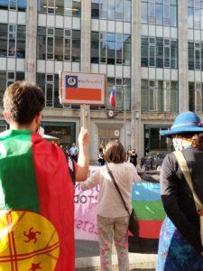 Aktivista con bandera mapuche levanta pancarta antifacista en frent de la emabajada de chile
